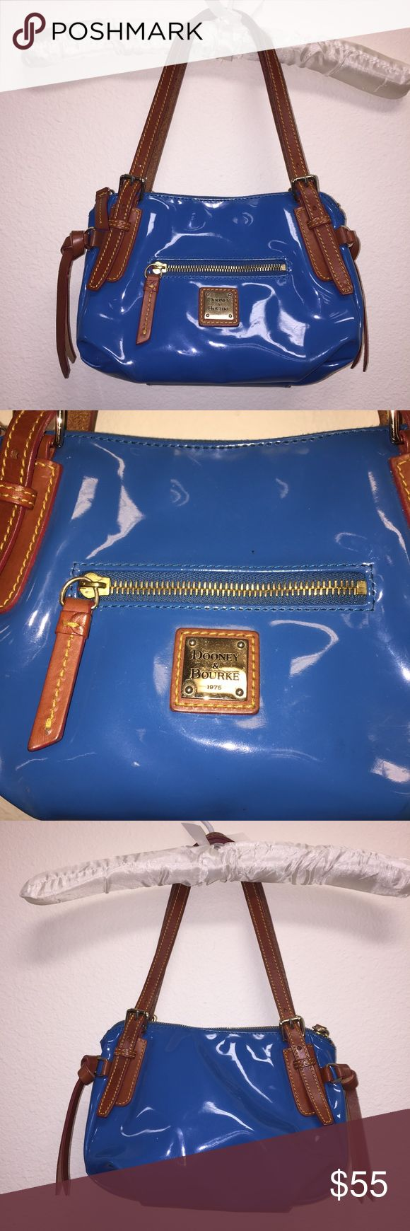 """Dooney & Bourke Electric Blue Shoulder Bag In excellent condition, very minimal blemishes if any. Bright blue with brown and gold accents and red lining. 9 1/2"""" wide, 7"""" high. Strap drop: 8''.Feel free to ask any questions, no trades/model photos. Offers thru offer button only! Items ship same day M-F if purchased before 2 pm PST! Dooney & Bourke Bags Shoulder Bags"""