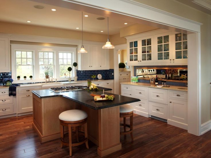 An unusual T-shaped kitchen island, which allows those perched on the stools to face each other, anchors this cottage-style kitchen. Deep blue subway tiles contrast with the cabinetry, a take on the classic nautical pairing of white and navy. A muted yellow wall color and warm-toned wood floors create an inviting charm throughout the space.