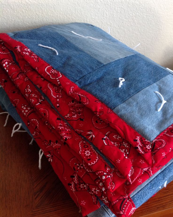 This unique, handcrafted jean quilt is the perfect addition to any room! It is handcrafted from recycled jeans and bandana-style cotton print fabric, insulated with batting, and tied off with matching yarn. The jeans are arranged in a unique rectangle pattern, and the cotton backing is a beautiful country-themed red print. It fits all standard-size full mattresses, and it is entirely machine-washable. This quilt is cozy, durable, and the perfect fit for your bed! -Dimensions: 5.5 x 9,5…