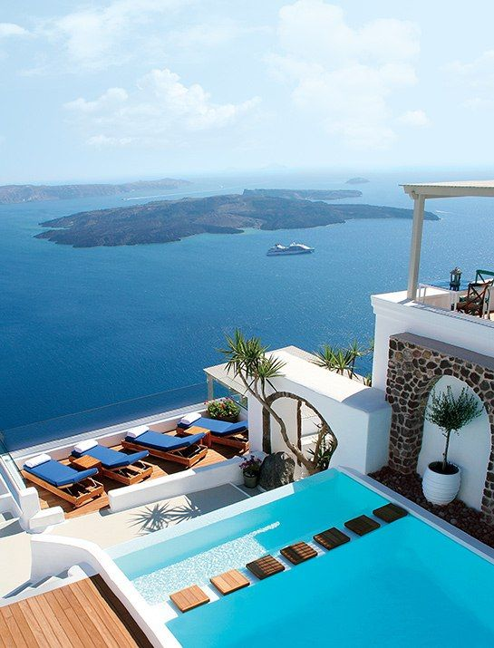 At the new Iconic Santorini hotel, carved into a cliff on the Greek island, everyday concerns seem to dissolve into the azure Aegean below.
