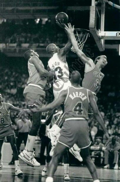 The GOAT maneuvers in the air through the Cavaliers' Tree Rollins, Ron Harper, and Craig Ehlo in Chicago.