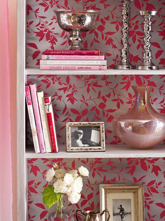 Gorgeous metallic wallpaper is the perfect partner for a shiny display space. Silver candleholders, sophisticated vases, and detailed photo frames shine in front of a pink-and-silver floral pattern on this bookshelf.