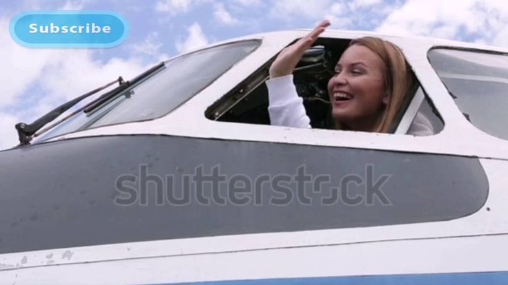 Beautiful young girl pilot sitting at the controls of an airplane | Stoc...
