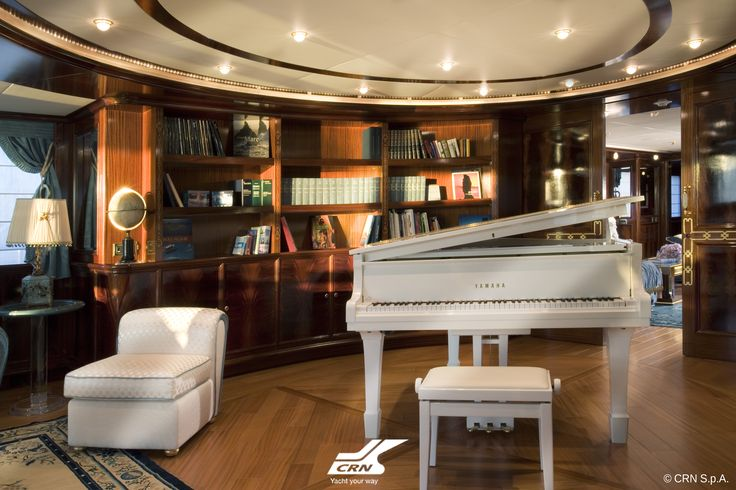 """CRN M/Y Blue Eyes of London ex Blue Eyes 60m is certainly a boat """"with a difference"""": abaft, on the main deck, where the guest area is commonly situated, one is immediately embraced by a huge semicircular library at the centre of which stands an imposing white grand piano which strongly contrasts the dark polished mahogany walls, a characteristic of all the woodwork all over the boat."""