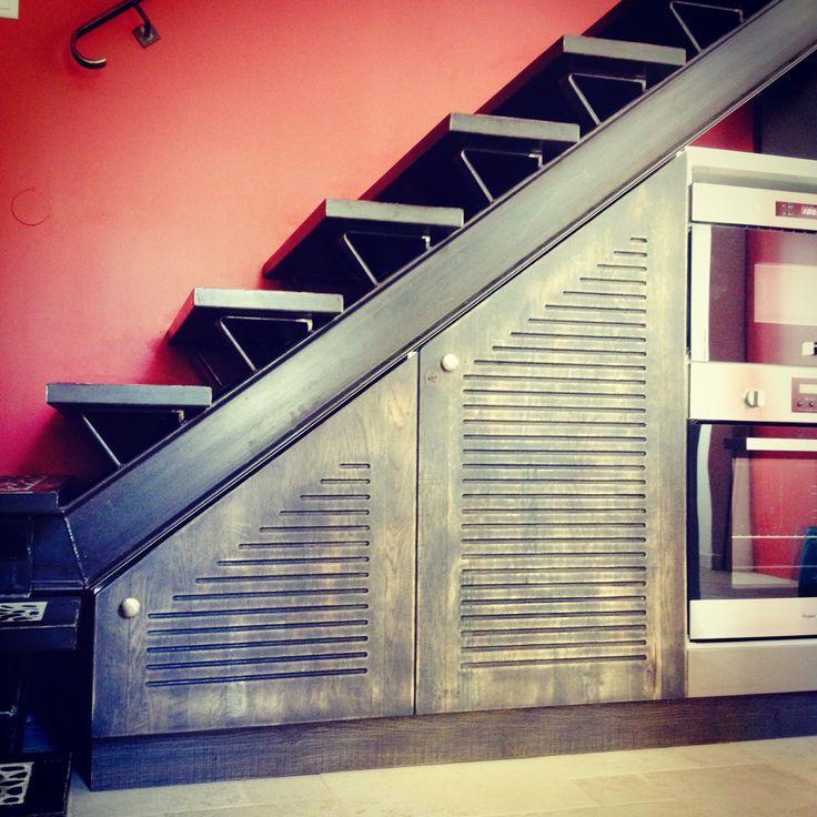 """Fabrication et installation de meubles de cuisine sous escalier. Motif des portes style persiennes, """"effet fumé"""" sur chêne pour un rendu industriel s'harmonisant avec l'ensemble de la cuisine. Les ..."""