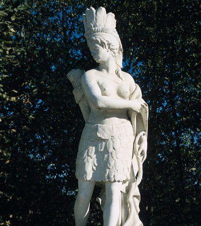 L'Amérique, statue allégorique du continent  Cette statue en marbre représente un Indien avec, à ses pieds, un alligator. A cette époque, pour les Européens, l'Amérique est le pays des Indiens, tireurs à l'arc, coiffés de plumes et réputés coupeurs de tête. Les alligators peuplaient alors le Mississippi.