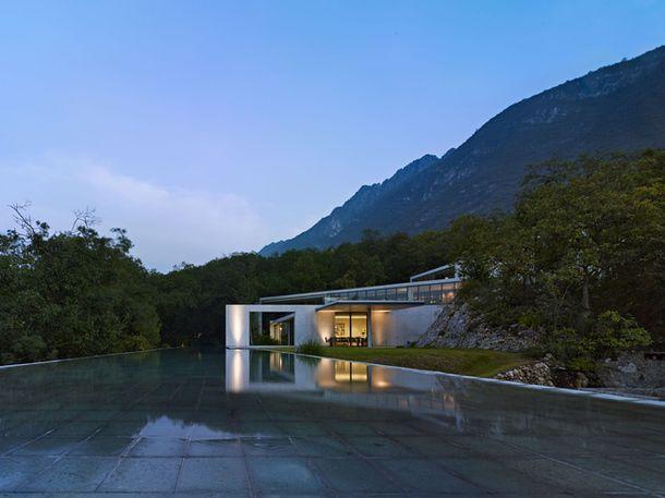 major water elements set against mountainous landscape distinct quadrilaterals shape building warmly lit interior