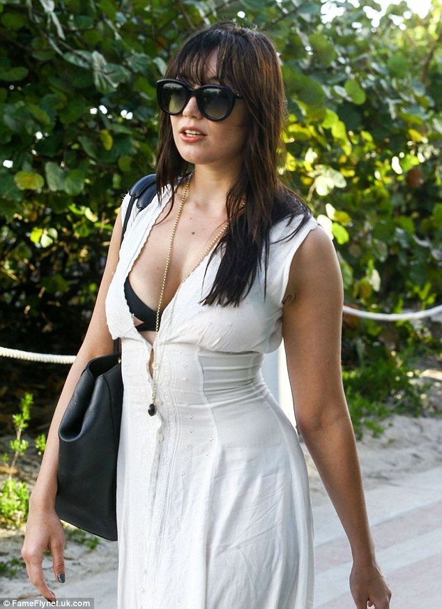 How Lowe can you go? Daisy Lowe finally opted to cover-up as she slipped into a stunning white dress pulled over her chic pink and black bikini while vacating a Miami beach on Monday - after hours of larking around in the idyllic waters