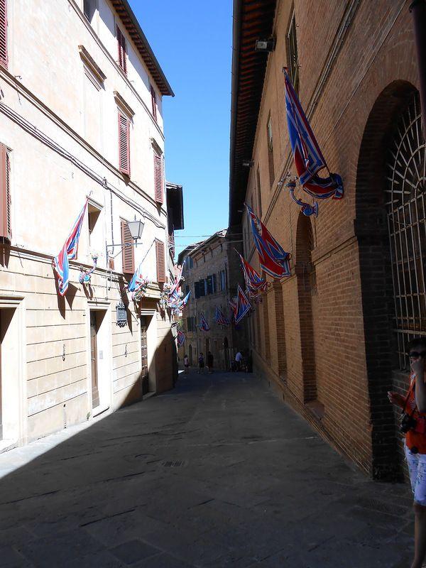Судя по знамёнам, эта улица в районе контрады Пантера. Контрады сложились в Средние Века, и основной их задачей было снабжать продовольствием и пополнениями войска, которые Сиена нанимала для защиты или для борьбы с Флоренцией.