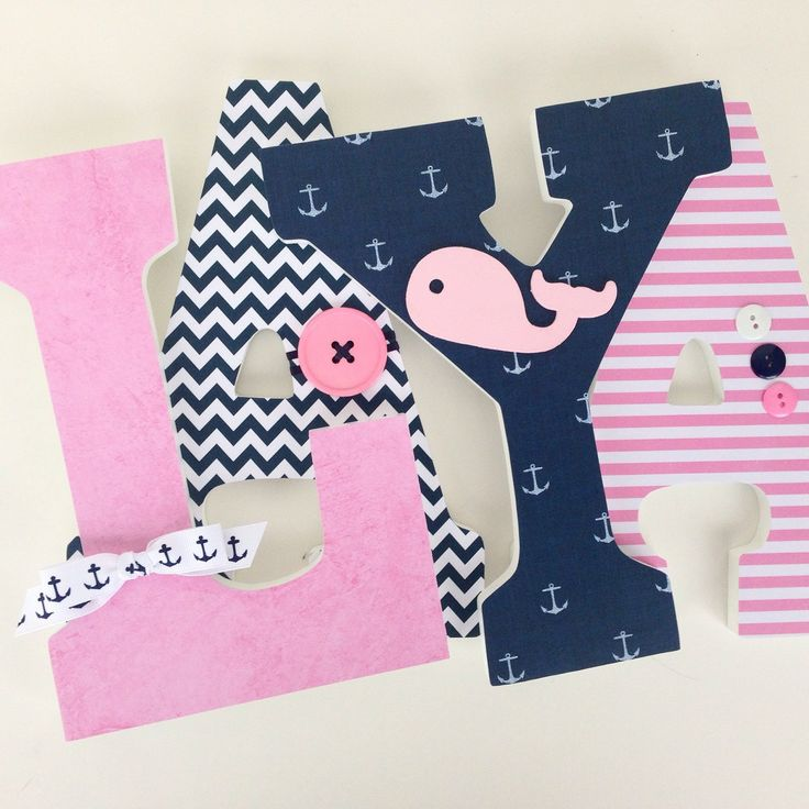 Navy blue and pink nautical wood nursery letters with whale, anchor, button, and bow embellishments.