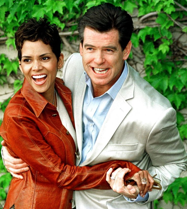 """Halle Berry and Pierce Brosnan pose for photographers in Cadiz, Spain before filming scenes for the James Bond movie """"Die Another Day"""", 2002."""