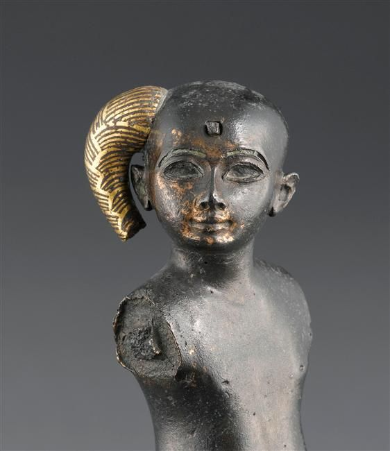 Bronze gilded statuette of seated Heru Pa Khart (Harpocrates), boy deity with the sidelock of youth. The face bears traces of past gilding, the whole statue was gilded. 1069-664BC. 22nd-26th dynasty. Egypt. Louvre museum, Paris.