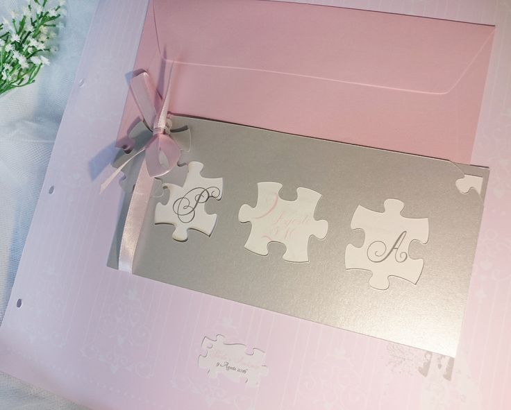 Partecipazione puzzle su carta argento con nastro in raso rosa e bigliettino bomboniera coordinato sagomato. Disponibile in altri 50 colori.