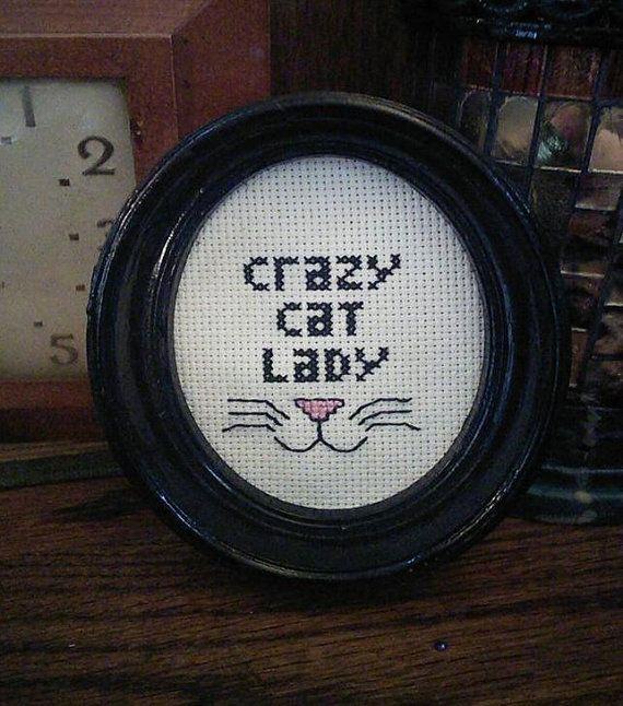 A cross stitch with the text CRAZY CAT LADY and a nose with whiskers. Includes frame (frame may vary from what is pictured.)