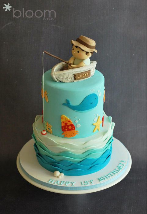 1st birthday cake with wave bottom tier, cut-out sea creature and baby fisherman and antique boat topper