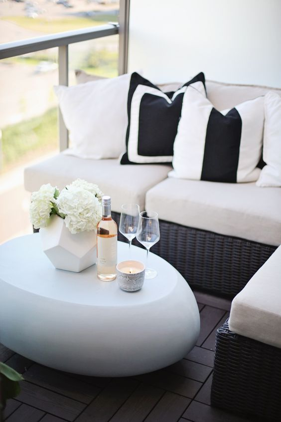a corner wicker bench with comfy cushions and a modern egg shaped white table