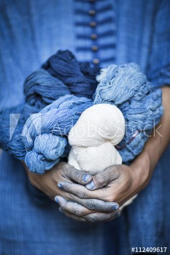 A man holding balls of yarn dyed with indigo