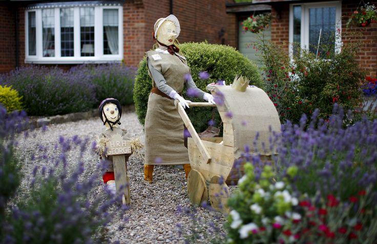 Orang-orangan sawah yang dibuat menyerupai Pangeran Inggris George dan Putri Charlotte dengan pengasuh mereka dipasang di sebuah kebun dalam Festival Orang-orangan Sawah di Heather, Inggris.