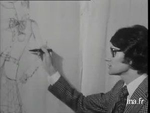 1968 YVES SAINT LAURENT dessinant une robe au fusain