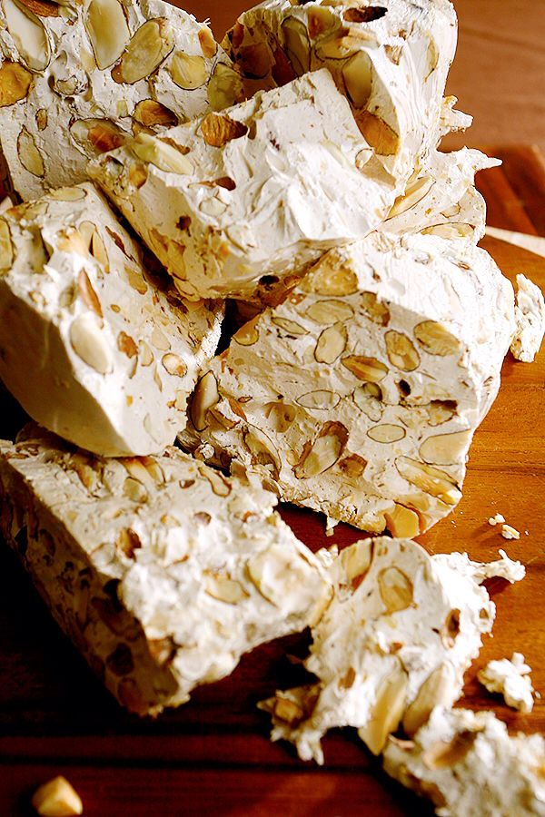 """In Italy, torrone is a traditional Christmas dessert—a sweet, toasted-almond candy—with many famous regional variations. The term """"torrone"""" probably comes from the latin verb """"torrere,"""" or to toast, referring to the toasted almonds. Today, there are many different types of torronne available—some soft, some hard and some with chocolate—not just in Italy, but worldwide. Torrone from Sicily, Abruzzo, and the cities of Siena, Alba, Cremona and others are especially renowned."""