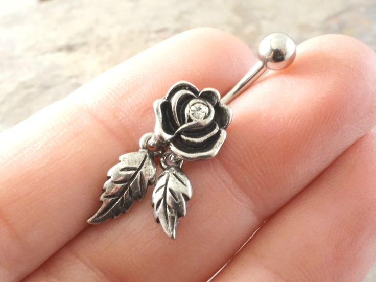 """Rose flower belly button jewelry ring with dangling leaves. Made entirely of 316L surgical steel, the barbell is 14 gauge and 3/8"""" long. The rose has a crystal center and leaves are highly detailed wi"""
