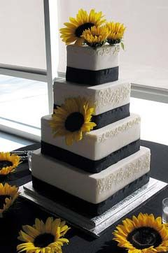 Four tier square black and white wedding cake decorated with yellow sunflowers
