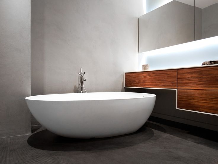 Modern bathroom in our bachelor pad loft features a freestanding Agape Spoon XL bathtub, Axor Strack faucet, concrete wall, walnut Millwork with corian counters and led accent lighting