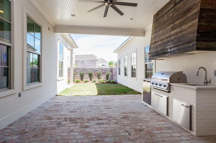 Open concept outdoor kitchen situated in a brick patio features an oversized reclaimed wood vent