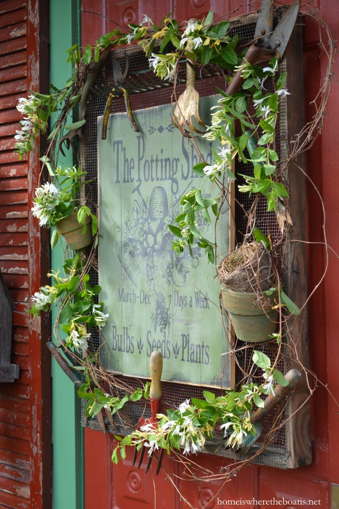 potting shed sign on door with vintage garden tools pots grapevine and honeysuckle