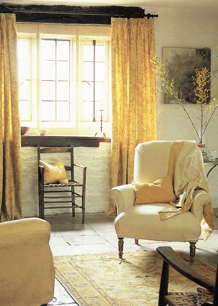 Simple, cottagey interior with drapes from a thin iron pole and rug on a bare flagged floor.