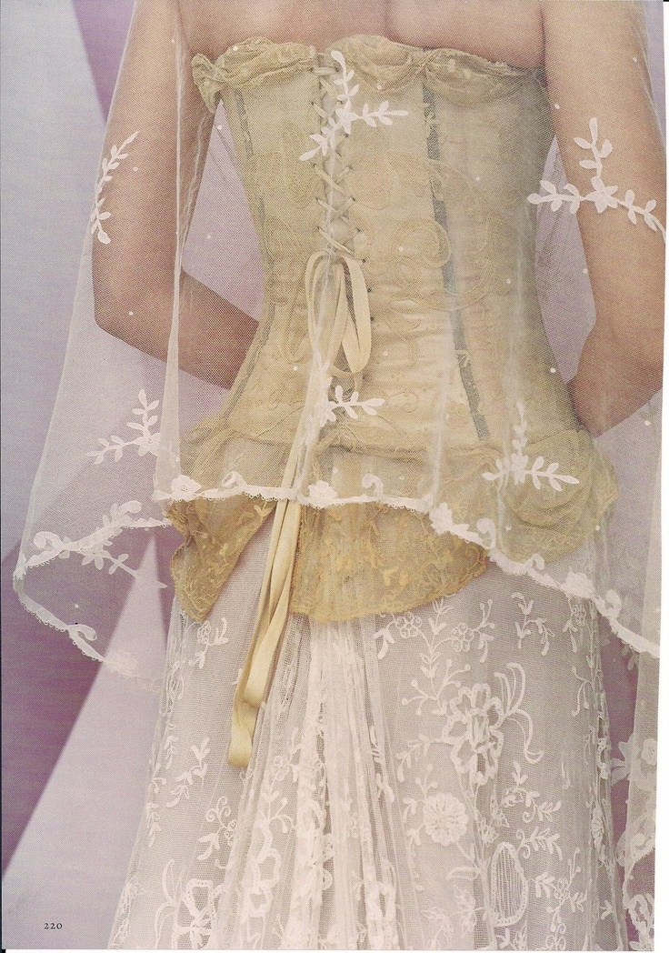 The corset of gold silk, lace, and ribbons is worn over a skirt of ivory re-embroidered lace; both are by Maggie Norris Couture. A shawl of gossamer handmade lace from Jana Starr Antiques & Bridal covers the bride's shoulders.