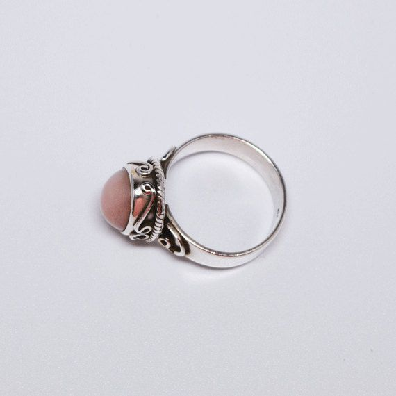 Pink Opal Silver Ring  Your are looking at an intricate Pink Opal ring made using sterling silver.  Pink Opal is said to heal matters of the heart, the pink opal meaning encourages the release of fear, worry or anxiety. It helps to dissipate stress, allowing you to be calmer. If you often find yourself nervous or anxious, try carrying pink opal stones with rose quartz, blue lace agate and other calming crystals to soothe your nerves. If you are healing from a break up, or the loss of a…