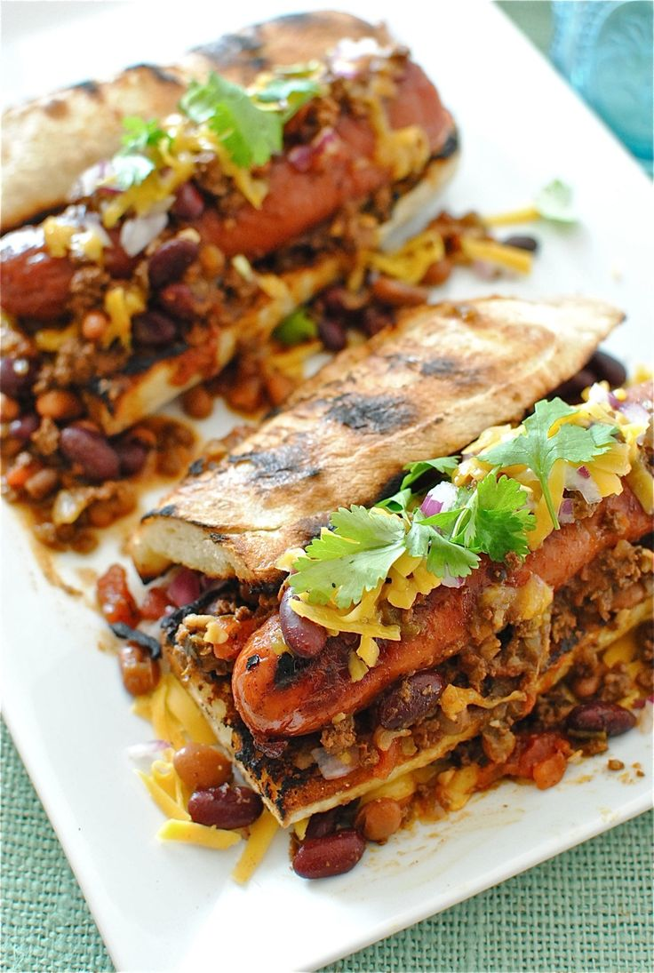 gourmet deluxe chili dogs on a grilled baguette with garlic, smoked paprika, red wine, tomatoes, brown sugar, and honey....