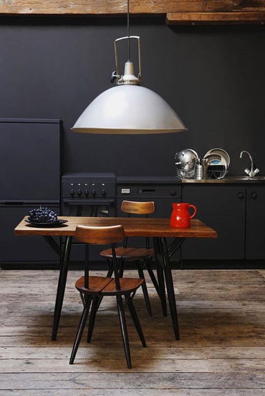 Matt black industrial kitchen. The hude industrial light fitting hung low above the table makes a beautiful centrepiece