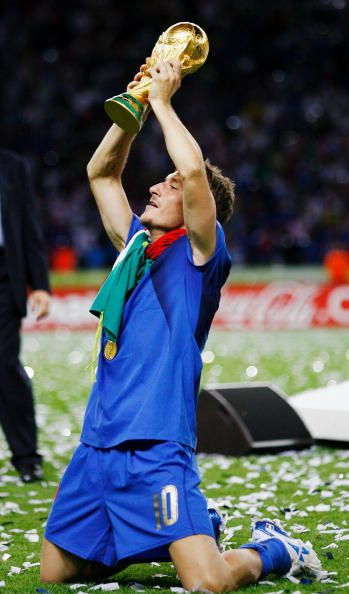 Francesco Totti of Italy holds the World Cup trophy aloft following his team's victory in a penalty shootout at the end of the FIFA World Cup Germany...
