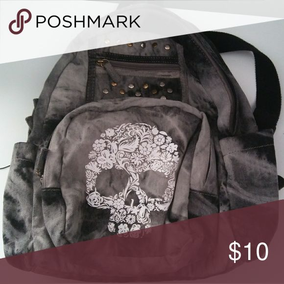 Skull backpack This backpack is a washed black tie dye pattern with gray, a skull printed on the big pocket on the back, and some studs for decor which are all in tact. Features one big pocket with one small zippered pocket inside, a small slit pocket on the outside, a smaller outer compartment, and a water bottle pocket on either side. Fabric feels like denim. Adjustable straps. In good shape overall. Xhilaration Bags Backpacks