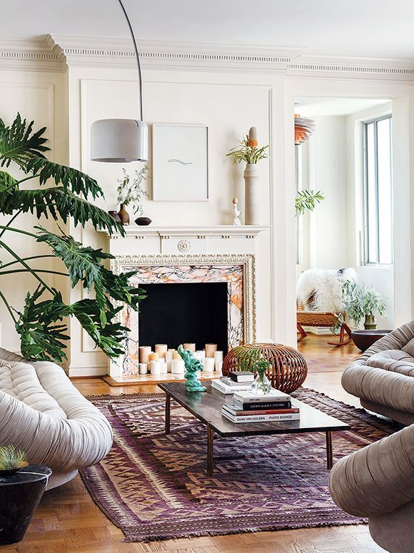 Eclectic bohemian-inspired living room with leather clamshell sofas and chairs, a vintage Moroccan area rug and candles in the painted fireplace.