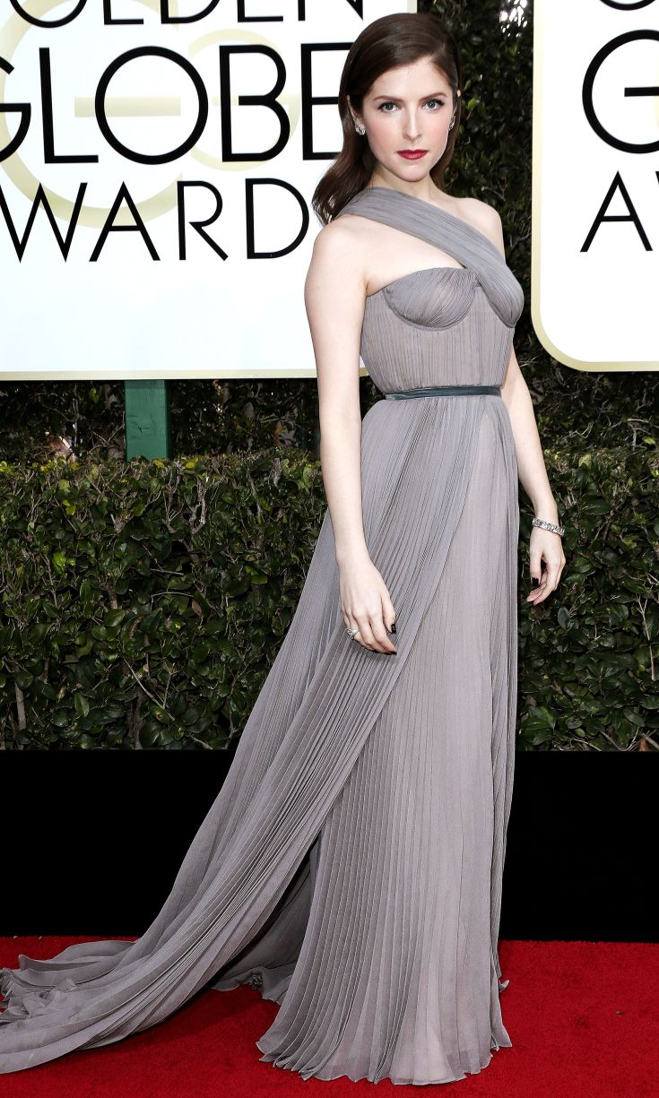 ANNA KENDRICK dons a dove-gray Vionnet gown with a pleated skirt, cross-body strap and train.