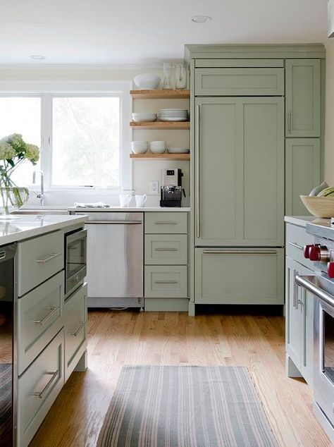 Beautiful kitchen features sage green cabinets paired with white quartz countertops. A sage green kitchen island is fitted with a microwave nook alongside a green striped runner. A stainless steel apron sink and gooseneck faucet stands below windows flanked by stacked floating shelves beside a sage green paneled refrigerator.