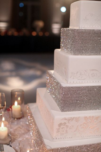 Get square cake stands, cover them with rhinestones and then put them between the cakes