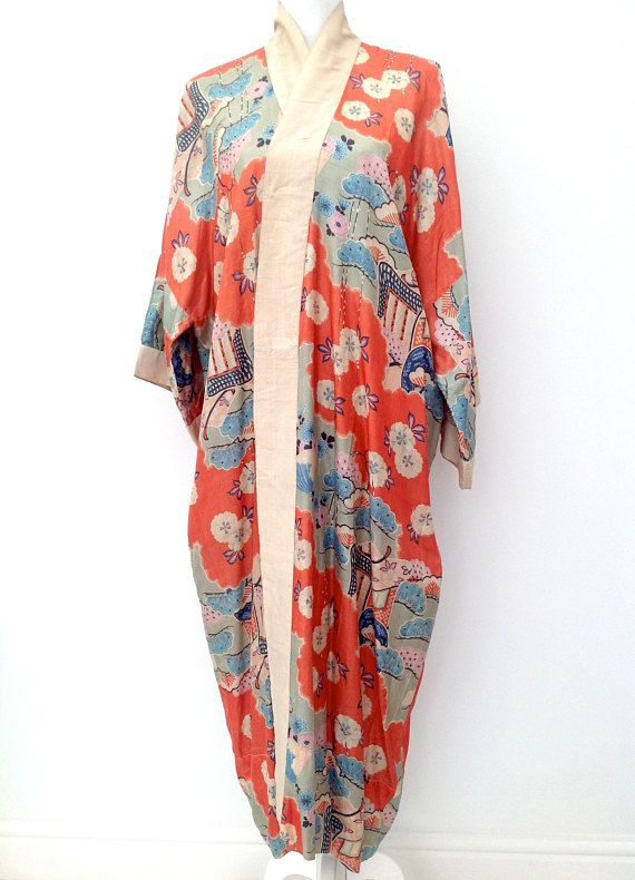 Here is a beautiful 1920s raw silk pongee Japanese export kimono robe in a rare shade of orange with pale green, blue and lilac coloured highlights. It has an all over design of flowers, leaves, fans and geometric shapes and has an embroidered name label which says Margaret Wallace to the