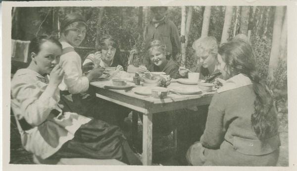 [Six women eating around a table at a camp] | saskhistoryonline.ca