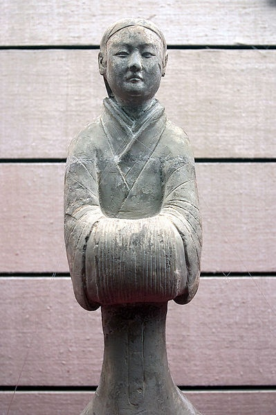 A Chinese Han Dynasty (202 BC - 220 AD) ceramic figurine of a lady servant with hands placed in front and covered in long silk sleeves.