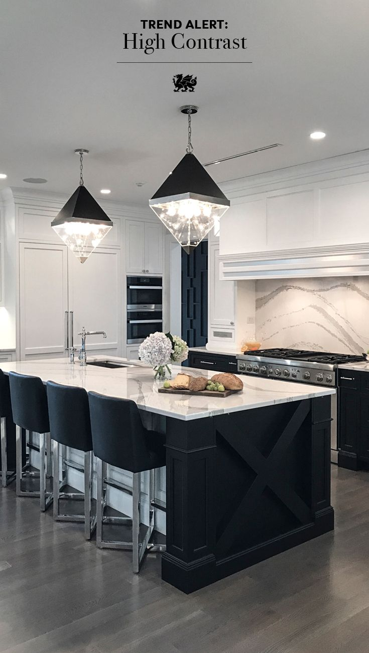 This black and white kitchen is always dressed for the occasion with timeless style and sophisticated details. The Brittanicca backsplash showcases powerful movement while diamond pendant lights highlight the luxurious kitchen island. Brittanicca, an ideal alternative to marble countertops, creates chic contrast with the black cabinetry. Upper white cabinets keep the look bright, balanced, and elegant. Design by AFT Construction #kitchenlighting #twotonecabinets #whitequartzcountertops