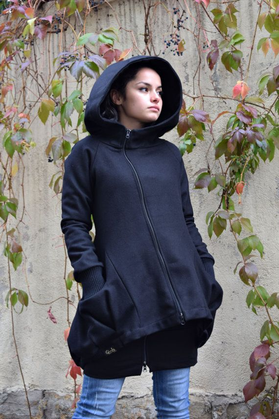Amazing black winter coat with big hood for a cozy holiday season. This amazingly soft designer coat is a stylish piece to wear. The asymmetric design adds a dash of extravagance to your appearance. Its wool and cashmere fabric makes this a warm coat while the lack of cotton lining on the inside keeps it less bulky and roomy enough to layer something underneath. Its loose design is flattering to any body shape and slims down your silhouette. The large hood is both a practical addition and a…