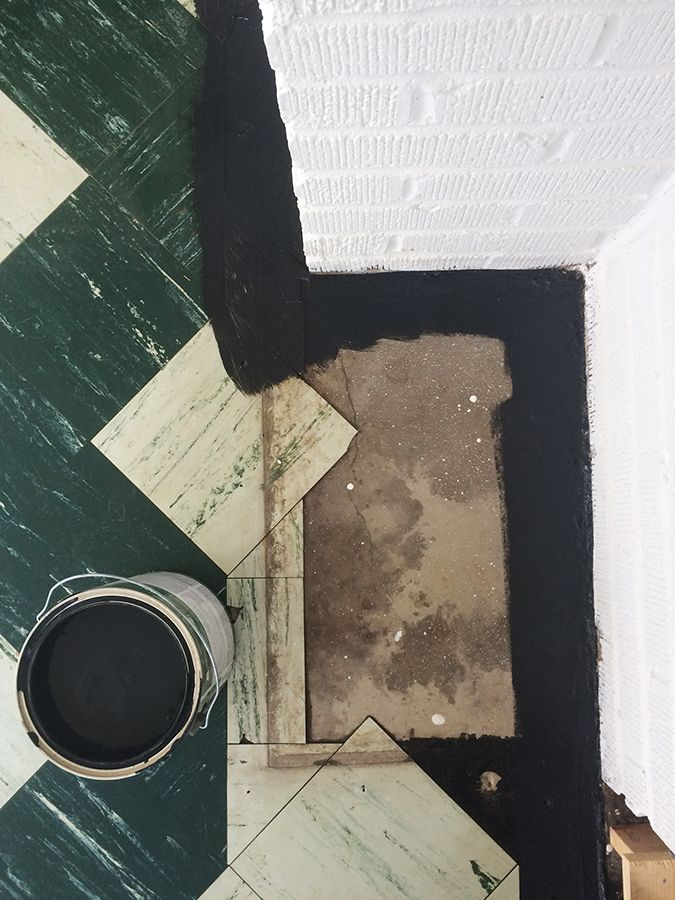 We painted the old, dates asbestos tile we found beneath our carpeting with black porch & patio paint for an instant update in our living room!