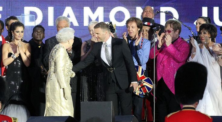 Gary Barlow of Take That, who organised the concert, shares a word with Her Majesty as Shirley Bassey, right, and Cheryl Cole, far left, lead the applause