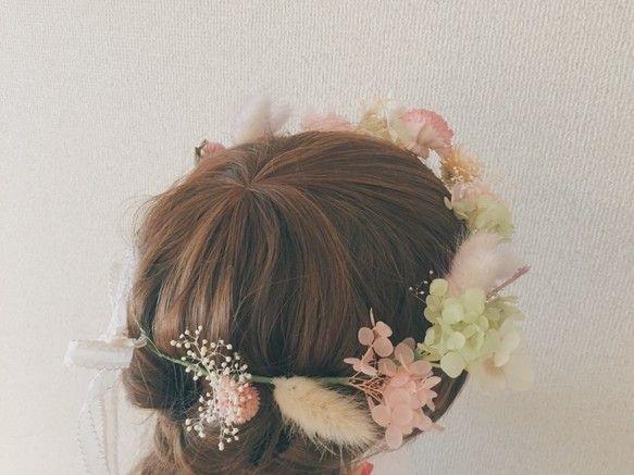 ピンク色のドライフラワーとプリザーブドフラワーを使用し、ナチュラルで優しさあふれるデザインに仕上げました。一部に造花を使用しています。女性らしい華やかな色合いですので、結婚式にもピッタリです。マネキンが装着している花冠とは若干並びが異なりますが、使用花材とボリューム感は同様です。♡使用花材ドライフラワー:ラグラス、センニチコウ、ヘリクリサム、ソーラーシフォンカーネーション、グラネットプリザーブドフラワー:あじさい、かすみ草、造花:白いあじさい※本物のお花をメインに使用しておりますので、大切に扱っていただき、直射日光を避けて保存してください。