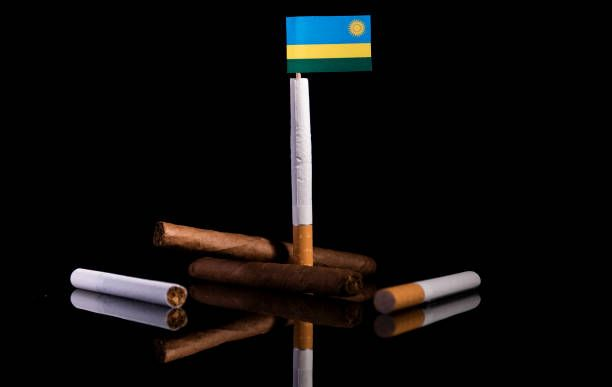 rwanda flag with cigarettes and cigars tobacco industry concept