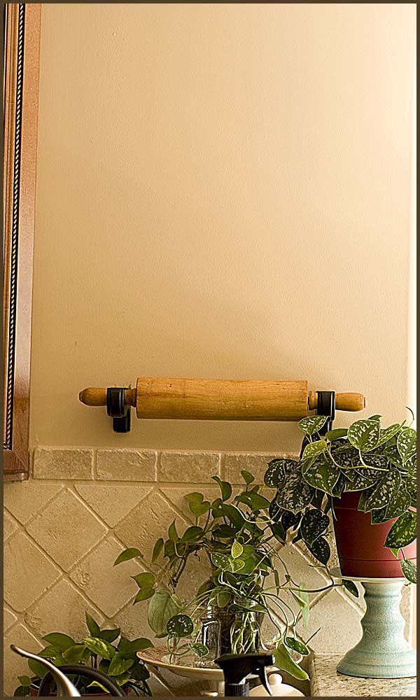 hanging rolling pin on wooden curtin rod holders. Smart! I have a gorgeous copper rolling pin this will be perfect for!